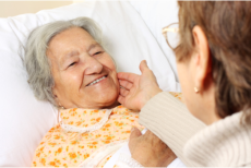 a patient lying while her caregiver holds her face