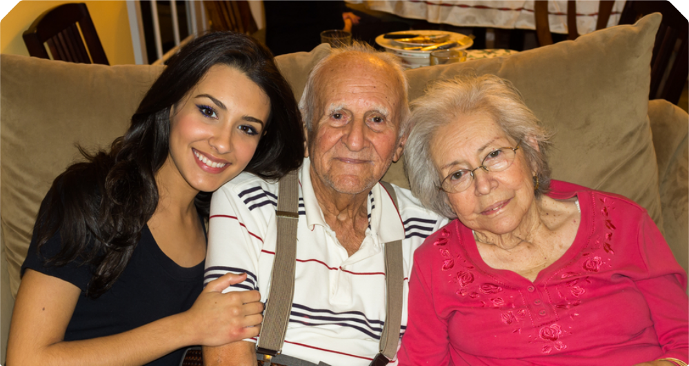 An elderly couple with their caregiver smiling